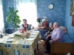 Голубева Л.А. получает поздравления от друзей за большим столом